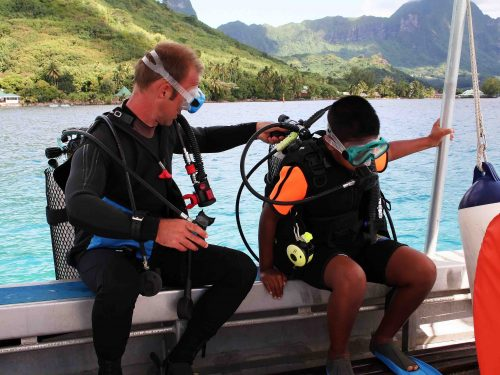 Scuba instructor and kid taking a lesson, preparing to jump off the boat